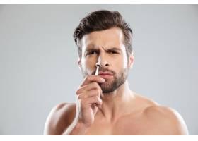 一名困惑的男子试图用镊子把头发扎进鼻子里_8076190