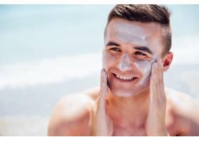 一名面带微笑的男子把晒黑霜涂在脸上在海_2583501