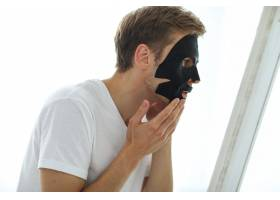 戴黑色面膜的男子皮肤净化木炭美学观_8423956