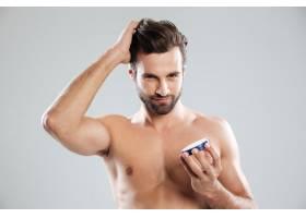 男士把头发拉直拿着隔离的面霜_8076288