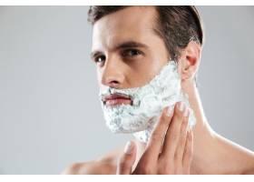 聚精会神的男子孤立地站着脸上涂着剃须泡_8078002
