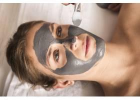 美丽的年轻女子在脸上涂抹面膜_3453480