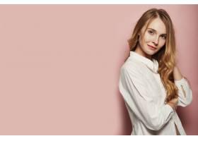 漂亮的年輕女子在粉色背景上擺姿勢_6435526