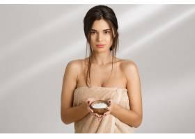 性感的女人手里拿着盐身体磨砂膏直视着_8357985