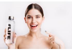 白墙上迷人的微笑模特快照素颜女孩指着瓶_12607349