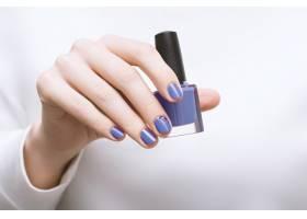 紫色指甲图案的女手拿着指甲油瓶_9130145