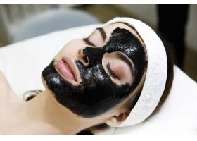 戴着黑色面具的女孩躺在温泉沙龙的桌子上_2447334