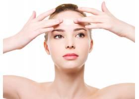 美容高加索年轻女子将保湿霜涂在额头上隔_10881177