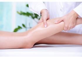 水療美容院美容師為女性美腿按摩_11182388
