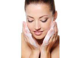 美丽的女人在石楠上用泡沫洗脸_10880981