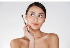 美丽的女人梳着发髻向上看拿着画笔画_6514596