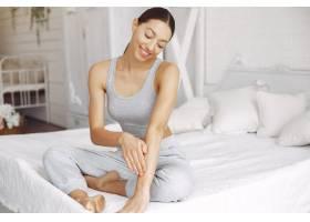 美丽的女孩坐在床上拿着美容产品_7169050