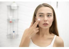 一位年輕漂亮的女士在浴室里用面霜涂抹臉部_1281281