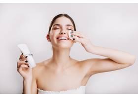享受面部水疗的快乐女人模特在涂抹面霜之_12607423