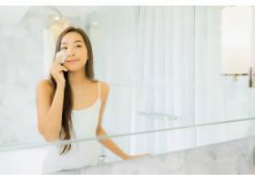 写真美丽的亚洲年轻女子为自己的脸检查和化_9289403