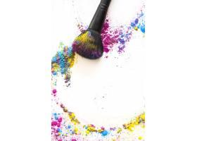 白色背景上的彩绘画笔和五颜六色的致密粉末_3614470