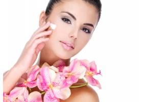 身体上有粉红色花朵的美女在脸上涂抹化妆品_12114961
