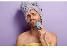 轻松严肃的留着胡茬的男士淋浴后擦拭脸部皮_12494380