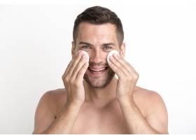 一名赤裸上身的男子在白色背景上用棉球擦洗_5223629