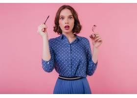 震驚的女模特穿著藍色衣服手里拿著睫毛膏_10658357