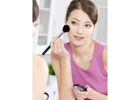 漂亮迷人的女人用刷子涂眼影照镜子_10872317
