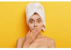 目瞪口呆的年轻女子脸上戴着天然的擦洗面膜_12496029