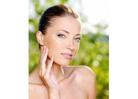 美丽性感的女人在眼睛附近的皮肤上涂抹化妆_11182324