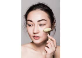 美丽的亚洲年轻女子在她完美无瑕的皮肤上涂_8473618