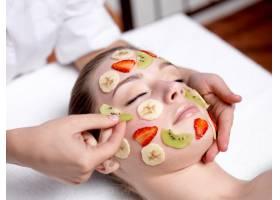 美丽的年轻女子在美容院接受水果面膜_10626032