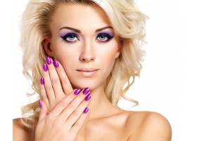 美丽的金发女子修剪紫色的指甲化着眼妆_11555531