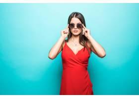 蓝色墙上穿红色连衣裙的漂亮年轻女子的肖像_11043924