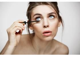 年輕漂亮的女孩在白色背景上染睫毛美容_9028132