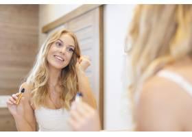 微笑的金發女子在浴室涂睫毛膏_10686908