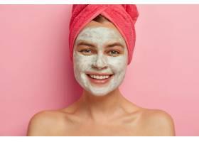 快乐的年轻女士在她美丽的脸上戴上美容面膜_12494872