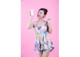 一位美麗的亞洲女子在粉色背景上拿著一瓶產_4524259