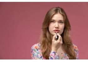 前景金发女子在粉色墙上涂红色口红_10860061