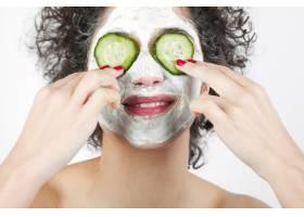 面带微笑的年轻女子戴着口罩把黄瓜片遮住眼_3196339