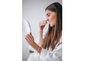 带镜子的女人用垫子卸妆_3964175