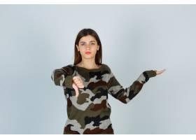 年轻的女士在假装穿着毛衣展示东西时向下竖_11620338