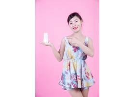 一位美麗的亞洲女子在粉色背景上拿著一瓶產_4524280