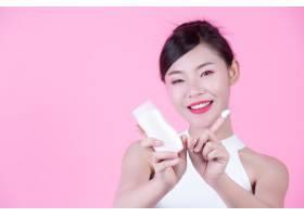 一位美麗的亞洲女子在粉色背景上拿著一瓶產_4527586