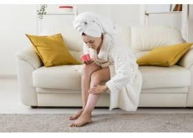 在家做水疗的女人用面霜保湿她的腿_9698350