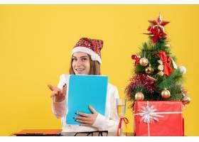 与圣诞节坐在一起的前视女医生在黄色背景上_11820015