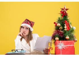 与圣诞节坐在一起的前视女医生在黄色背景上_11819884