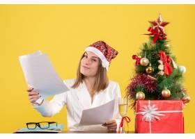 与圣诞节坐在一起的前视女医生在黄色背景上_11819900