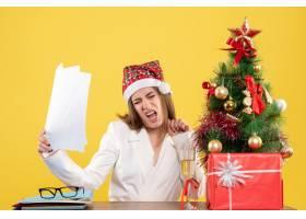 与圣诞节坐在一起的前视女医生在黄色背景上_11819910