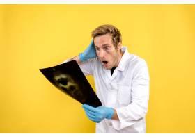 前视男医生手持X光片在黄色背景下进行内科_11960477