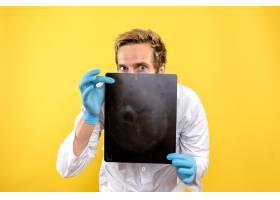 前视男医生手持X光片拍摄黄色背景内科手术_11960480