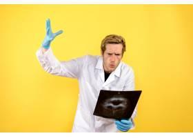 前视男医生拿着X光片在黄色办公桌上医生手_11960483
