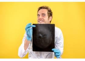 前视男医生拿着X光片在黄色桌子上看医生手_11960484